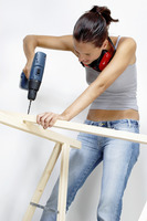 A woman drilling a hole on a wood