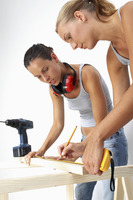 A woman helping her friend to hold a wood while she is marking the measurement