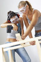 A woman helping her friend to hold the wood as she is drilling