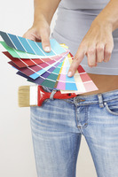A woman in jeans pointing at the selected colour from the colour cards
