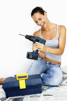 A woman in jeans sitting on the floor playing with a driller