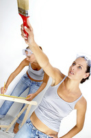 A woman is measuring a wood while her friend is painting the wall