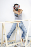 A woman with goggles and headphone using a driller to shoot at the camera
