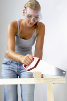 A woman with goggles sawing a wood