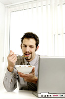 Businessman checking his work while eating breakfast cereal