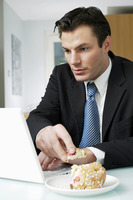 Businessman having breakfast while using laptop