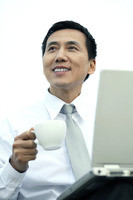 Businessman holding a cup while using laptop