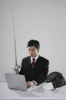Businessman holding fencing foil while using the laptop