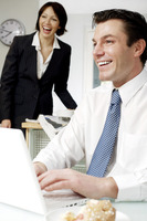 Businessman smiling while using laptop, wife in the background