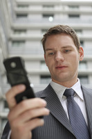 Businessman text messaging on his cell phone