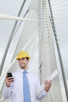 Businessman with roll of blueprints text messaging on the phone