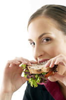 Businesswoman biting into a sandwich