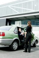 Businesswoman greeting her client from the taxi