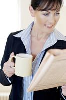 Businesswoman holding a cup while reading newspaper