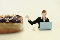 Businesswoman pulling out a chunk of doughnut while using laptop