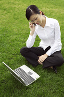 Businesswoman talking on the mobile phone while using laptop