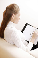 Businesswoman writing in an organizer