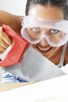 Close-up of a woman with goggles sawing a wood