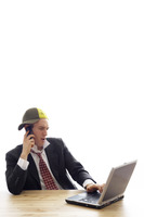Fashionable businessman talking on the cell phone while using laptop