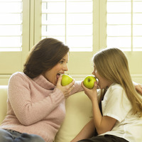 Mother and daughter sitting on the couch eating green apples