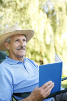 Senior man with hat reading book