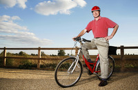 Senior man with safety helmet sitting on a bicycle
