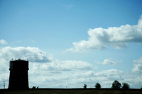 Silhouette of tower and trees on field