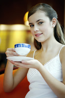 Woman enjoying a cup of aromatic coffee in a cafe