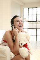 Woman hugging a soft toy while talking on the mobile phone
