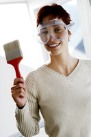 Woman in goggles holding a paintbrush