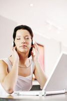 Woman listening to music on the headphones while using laptop