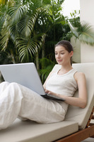 Woman sitting on lounge chair using laptop