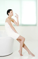 Woman sitting on the bathtub corner drinking a glass of water