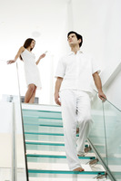 Woman text messaging on the mobile phone while her boyfriend is walking down the stairs