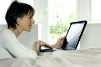 Woman using laptop in the bedroom