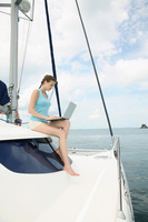Woman using laptop on yacht