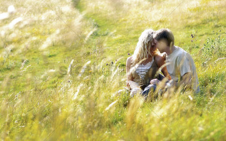 草 : A couple sitting on the grass kissing