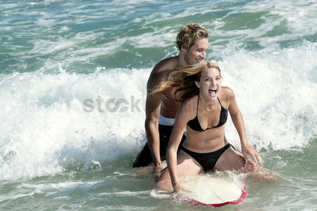 体育 : A couple surfing together on the sea