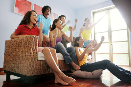 她 : A group of friends cheering while watching football match on the television