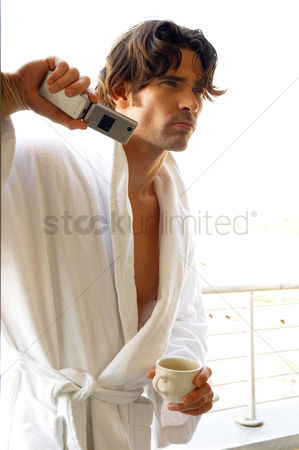 流动性 : A man in white bathrobe holding a cup and a hand phone