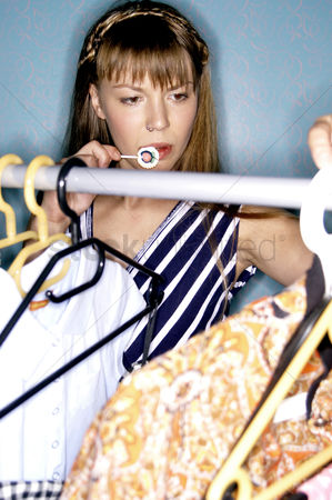 购物 : A woman eating lollipop while choosing her clothes