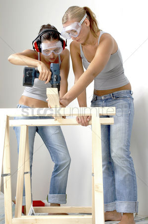 内饰 : A woman helping her friend to hold the wood as she is drilling