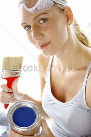 内饰 : A woman with goggles holding a brush and a tin of blue paint