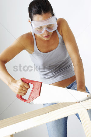 内饰 : A woman with goggles sawing a wood