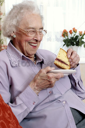食物 : An old bespectacled woman sitting on the couch eating cake