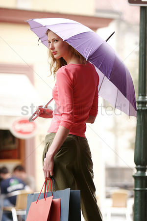 购物 : Back shot of a lady holding a purple umbrella and some paper bags