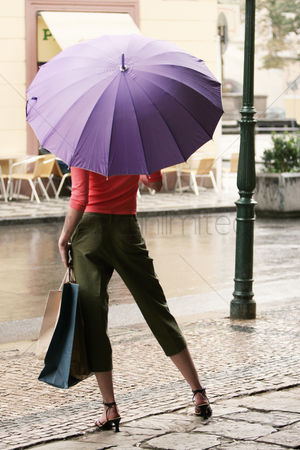 购物 : Back shot of a lady in high heels holding a purple umbrella and carrying paper bags