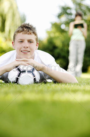 草 : Boy lying forward on the grass with his chin resting on a soccer ball