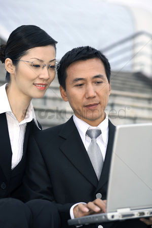 流动性 : Businessman and businesswoman sharing a laptop