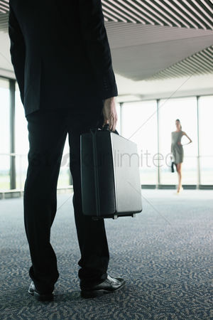 正式服装 : Businessman and businesswoman waiting for their flight in airport lounge